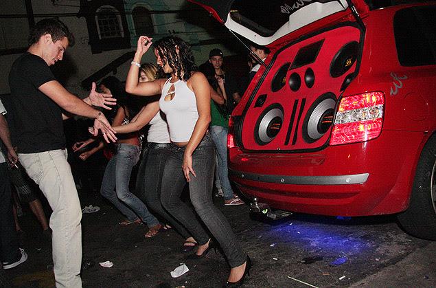 Jovens dançam ao lado de carro com som alto estacionado em rua na zona sul de São Paulo; dono do carro poderá ser multado