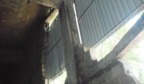 Cơ quan hữu trách dùng những mảnh tôn che đậy phần mảng bê tông bị bể ở gầm cầu vượt. (Hình: Thanh Niên)