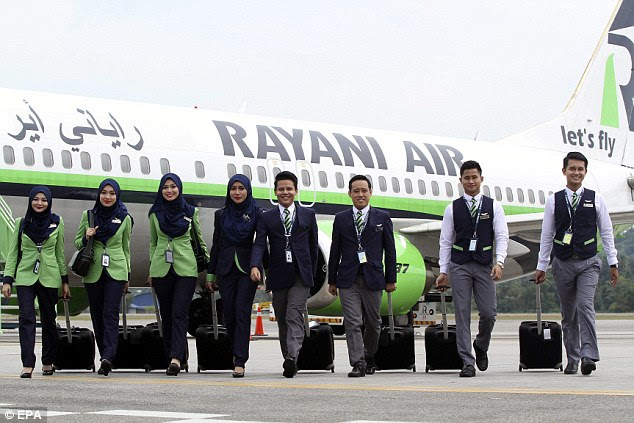 Cabin crew pose for a photograph in front of a Boeing 737-400 at Kuala Lumpur International Airport