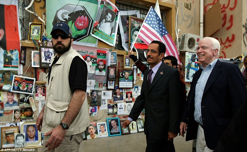 High profile visit: Republican senator John McCain visiting Benghazi today walks past the wall of the dead and missing with Abdul Haviz Ghoga, spokesman of the National Transitional Council