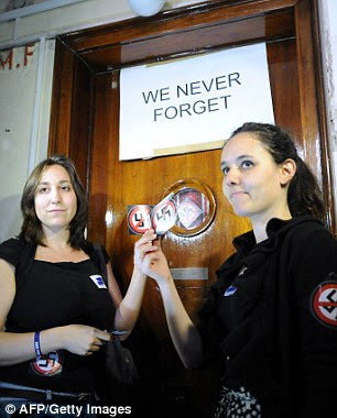 Activists hold up 'No Nazi' symbols in front of the door of Laszlo Csatary's hideaway building prior to their protest against him