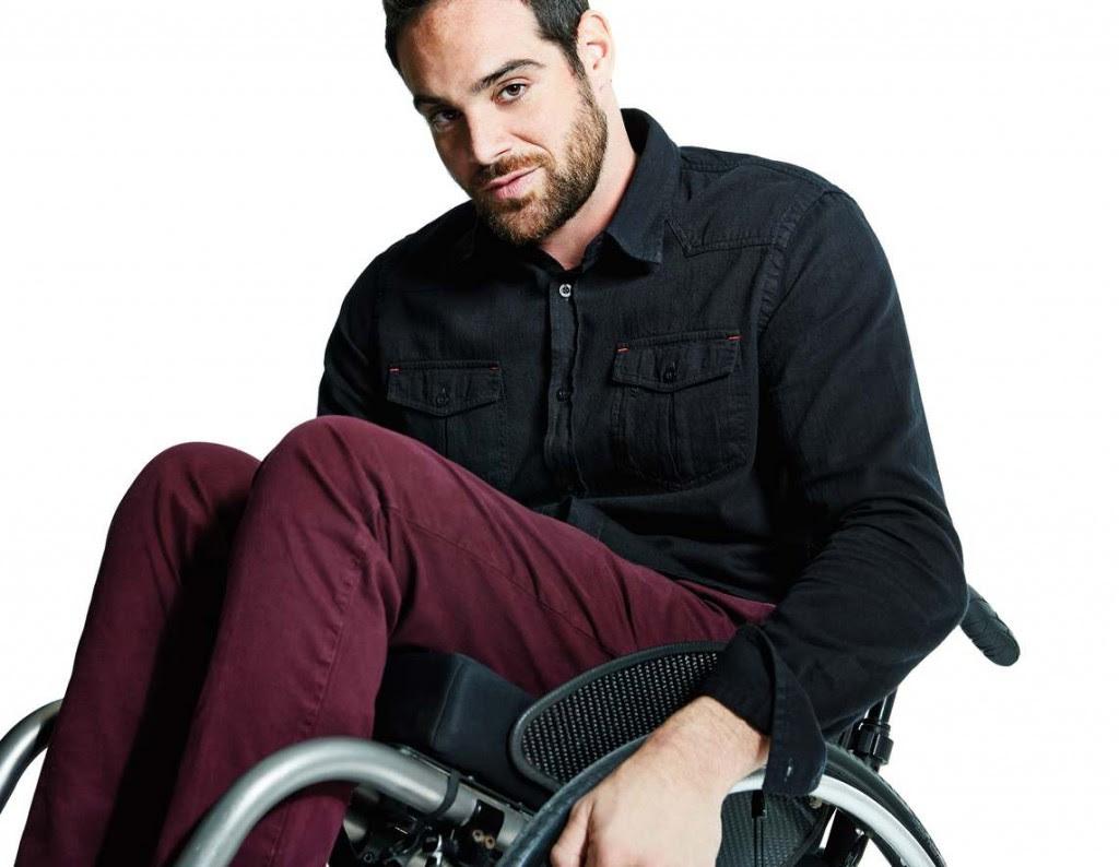 Modelo em cadeira de rodas veste blusao preto e calca vinho.