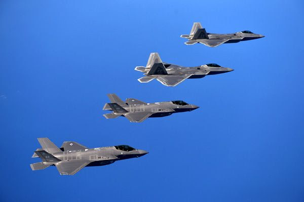 A pair of F-22 Raptors and two F-35 Lightning IIs fly in formation for a training mission.
