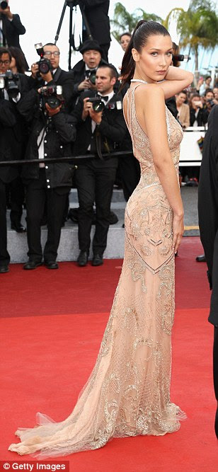 Glamour puss: Her slender frame was highlighted by the form-fitting dress which featured gold lace and bronze sequin detailing