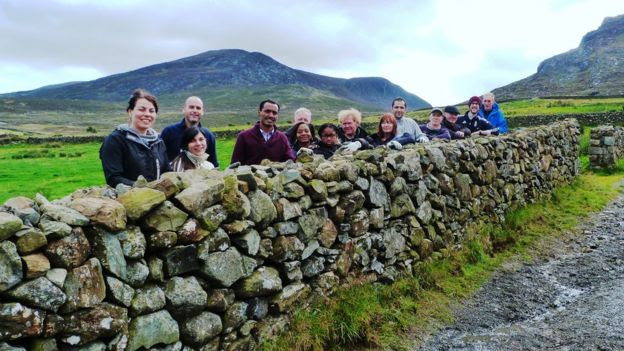 Volunteers pictured next to a repaired dry-stone wall in the Mournes
