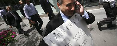"Joshua Persky, an unemployed financial engineer, takes a phone call from an interested employer Tuesday, June 24, 2008 in New York. Persky, wearing a pinstriped suit and an ""MIT Graduate for Hire"" sign draped over his shoulders, lost his job six months ago as an investment banking consultant. He has been handing out his resume on the sidewalk. (AP Photo/Mark Lennihan)"