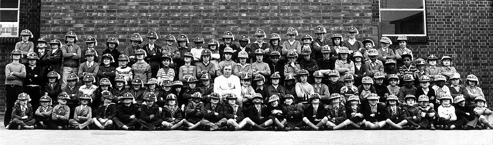 If the caps fit: Bobby Moore poses in his England kit with 99 boys from the school opposite West Ham's Upton Park ground on the eve of his 100th game for his country in 1973
