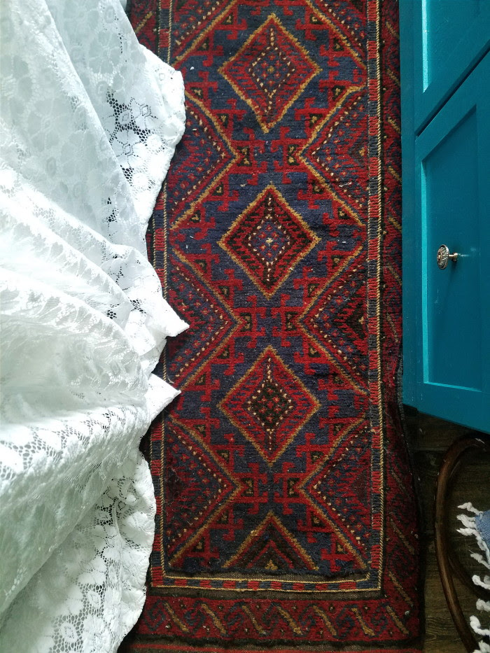 Maroon and navy runner rug with lace curtains and teal bathroom vanity