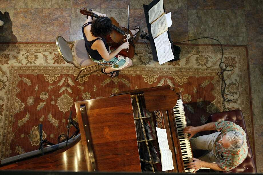 Rebecca Roudman (top) and Noel Benkman (bottom) perform works by Beethoven and Debussy during a classical music concert at the Cadillac Hotel in the Tenderloin district on April 11, 2014 in San Francisco, Calif.  The hotel has been regularly hosting concerts of all types for residents and neighbors for around 5 years. Photo: Codi Mills, The Chronicle