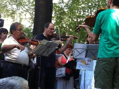 La 'Orquesta Solfónica', la banda del 15-M, interpreta música clásica en el Paseo del Prado - Foto: @letras15M