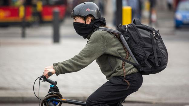 A cyclist bundles up against the smog