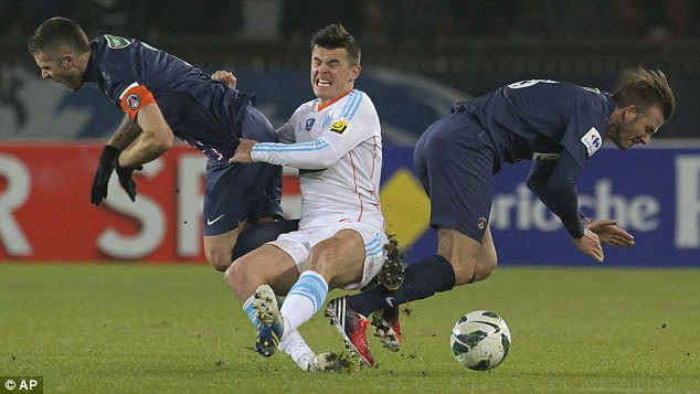 Le Crunch: Joey Barton takes no prisoners as David Beckham (right) is sent flying