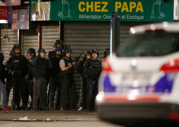 French police secure the area as shots are exchanged in Saint-Denis