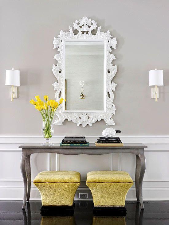 ornate mirror + chic console + bright colored ottomans