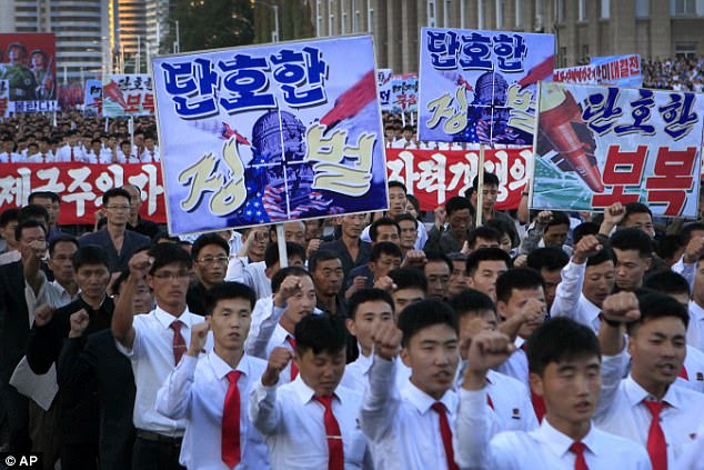 "rth Koreans gather at Kim Il Sung Square to attend a mass rally against America on Saturday. The sign on the left foreground reads ""decisive punishment"" while the sign on the right reads ""decisive revenge'"