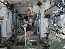 Bob Thirsk exercises with the Glenn Harness aboard the International Space Station
