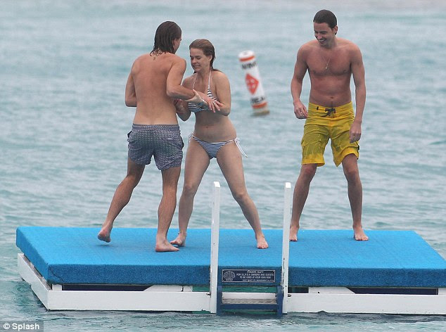 In you go! Climbing on board a jetty in the middle of the ocean, the trio demonstrated their sibling bond as they larked about and pushed each other into the water