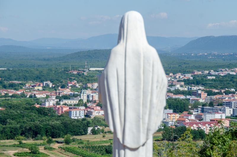 statue overlooking village