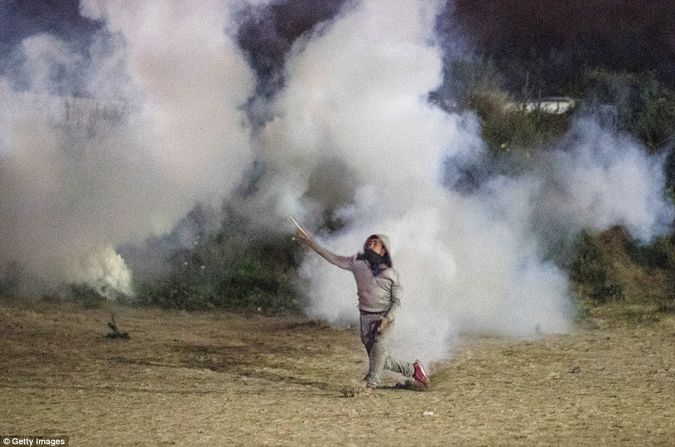This migrant is seen walking through the smoke in the camp amid chaos tonight, likely to continue well into tomorrow