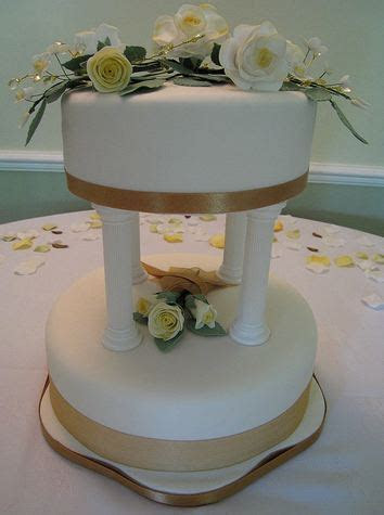 Two tier white wedding cake with Roman columns and white