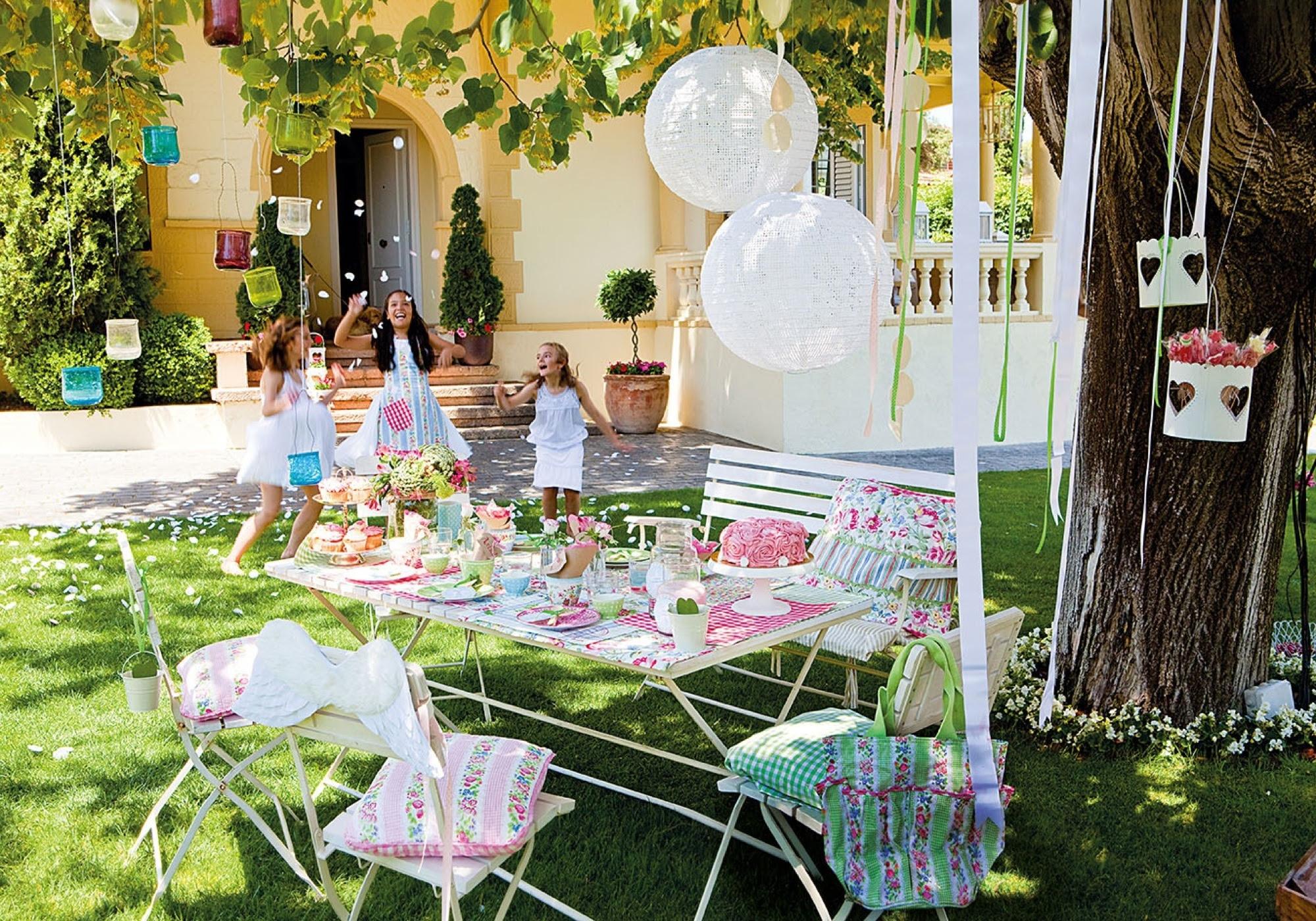 Jardín con mesa preparada para fiesta infantil con globos, manteles estampados verano, cojines 349250