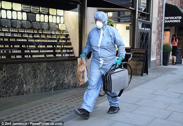 A forensic officer, wearing a blue boiler suit, arrives at the safety deposit business armed with evidence bags