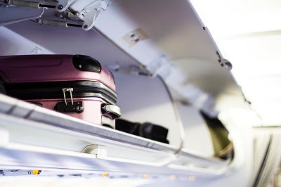luggage in overhead bin on plane
