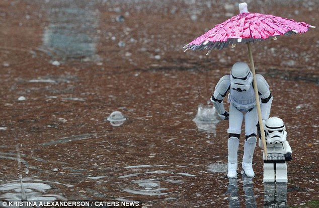 Any port in a Storm-trooper: The evil footsoldier cowers under a girly umbrella. He appears to be making his son hold it for him