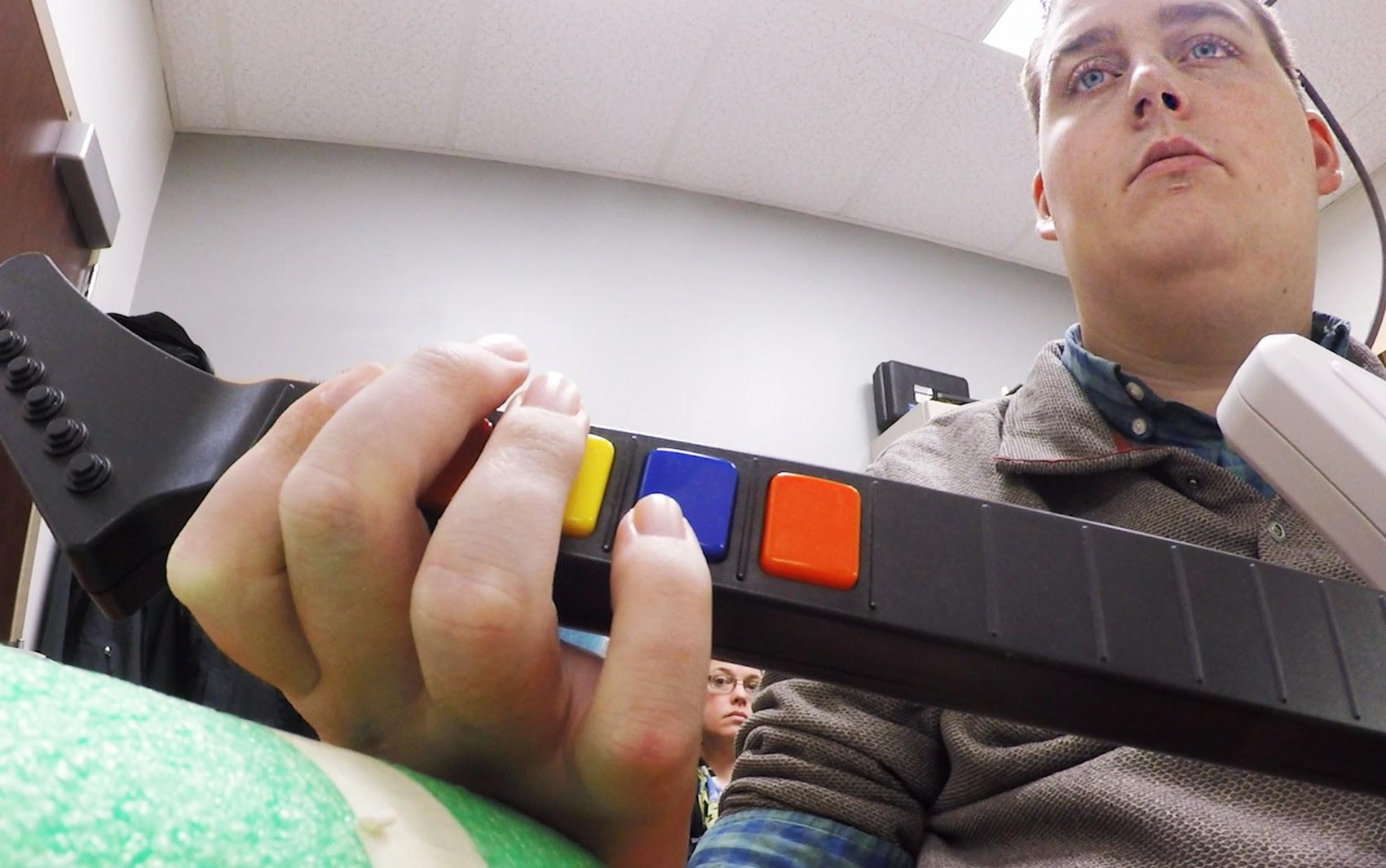 Ian Burkhart, de 24 anos, toca guitarra de videogame durante estudo com a tecnologia de bypass neural; chip no cérebro de Burkhart lê seus pensamentos, os decodifica e envia sianais a uma manga em seu braço que permite que ele mova suas mãos  (Foto: Ohio State University Wexner Medical Center/ Batelle)
