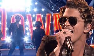 Bruno Mars takes the stage wearing rollers to promote his