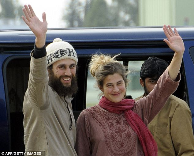 We're free: Swiiss couple Olivier David Och and Daniela Widmer wave upon their arrival at the Qasim base in Rawalpindi today after escaping Taliban capture