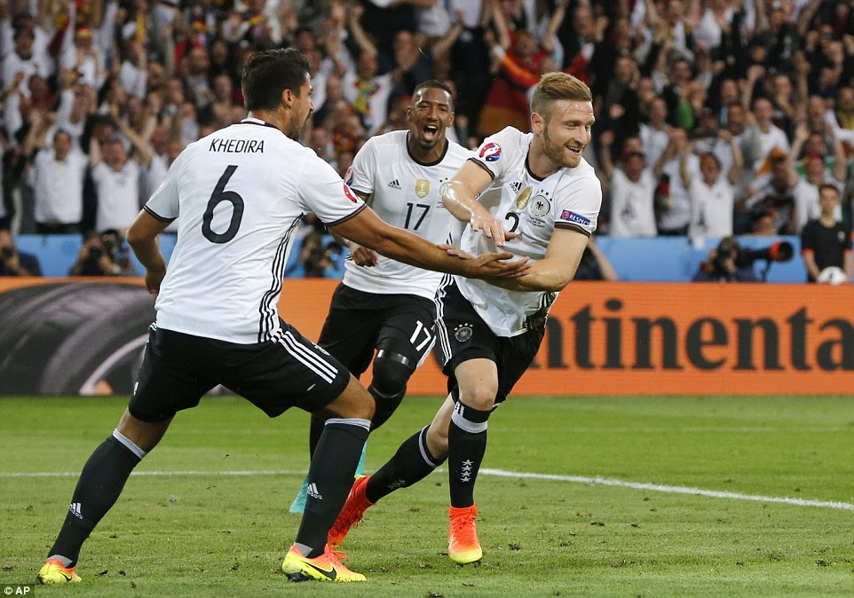 Germany's Shkodran Mustafi (right) celebrates with Sami Khedira (No 6) and Jerome Boateng (No 17) after scoring against the Ukraine