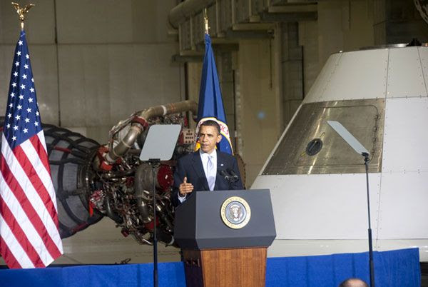 With a space shuttle main engine and an Orion capsule mock-up behind him, President Obama makes a speech about his plans for NASA at Kennedy Space Center, on April 15, 2010.