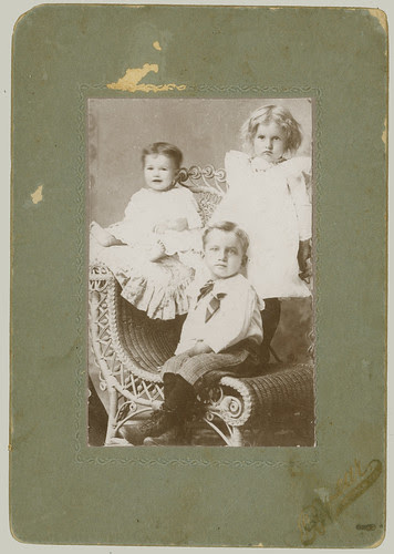 Three children and rattan chair