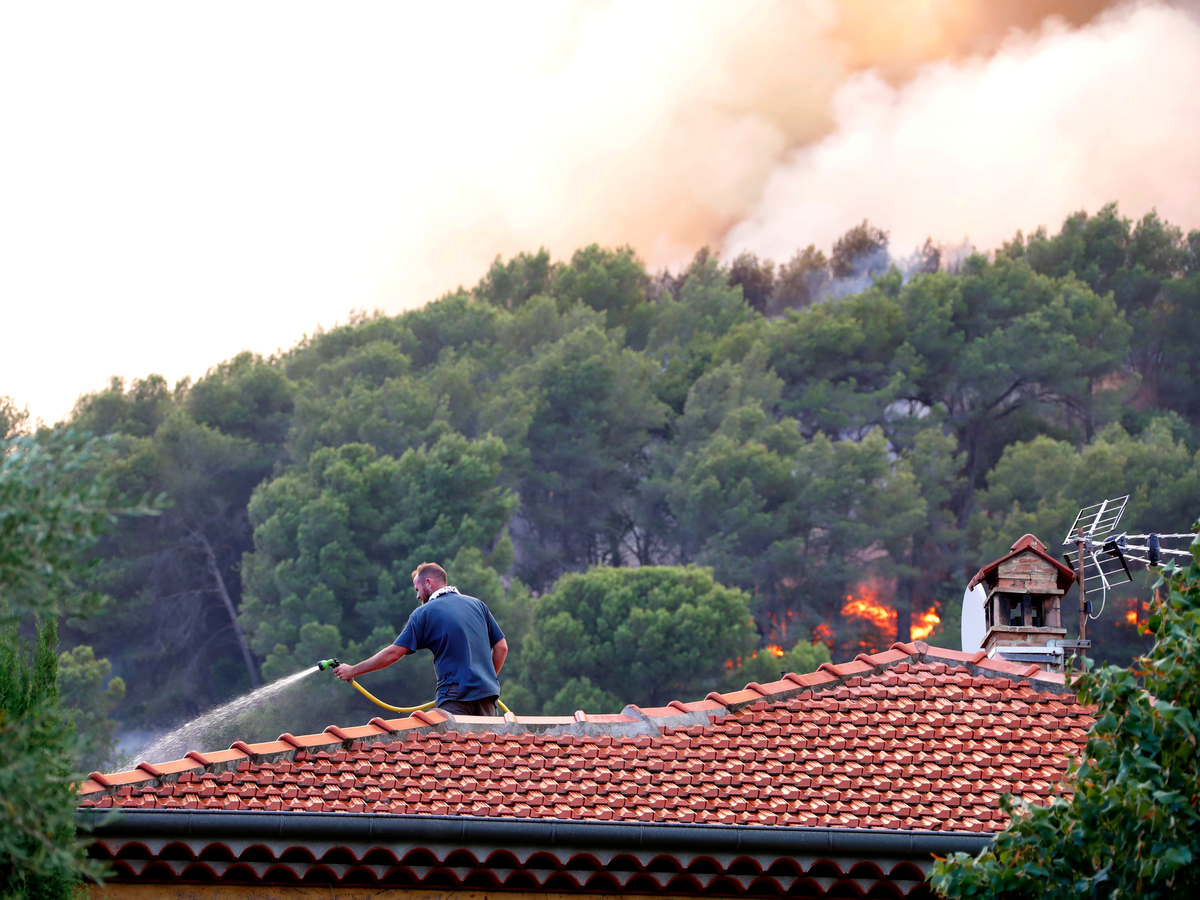 Some took matters into their own hands — this man doused his roof with water to make it more flame-resistant.