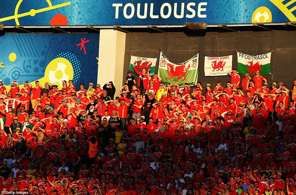Wales' supporters that are caught in the sun shield their eyes from the light in their section at theStadium Municipal