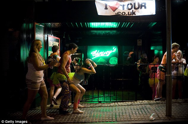Shameless: A passerby cheers as two partygoers get up close and personal outside an Irish-themed bar