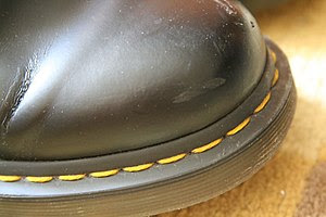 Distinctive yellow stitching on Doc Martens shoes.