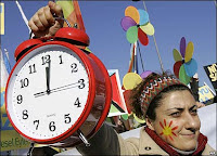 Greenpeace campaigner holds an alarm clock during a climate change rally in Istanbul, Turkey