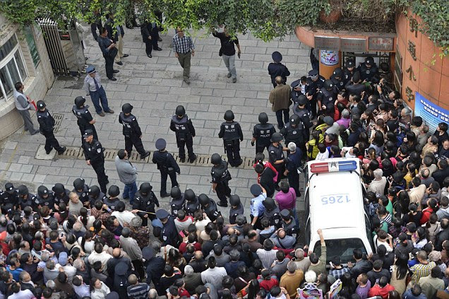 Police officers form a perimeter atKunming's Mingtong Primary School insouthwestern China today following a stampede which left six young pupils dead and 25 injured