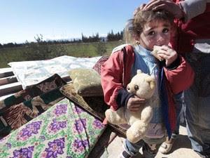 Criança síria que, com a família, fugiu de Homs é vista nesta segunda-feira (5) em Qaa, junto à fronteira com o Líbano (Foto: AP)