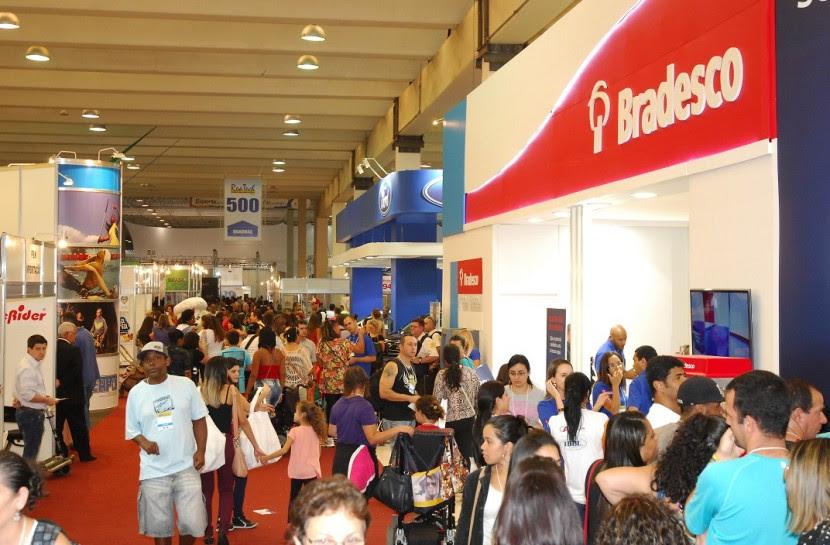 Foto de um pavilhão com multidão visitando stands de diversas empresas.