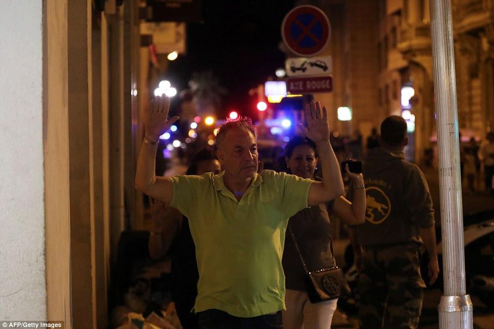 As pessoas que saem da área foram obrigados a manter suas mãos para cima como eles evacuaram a cena perto do mar em Nice na noite passada