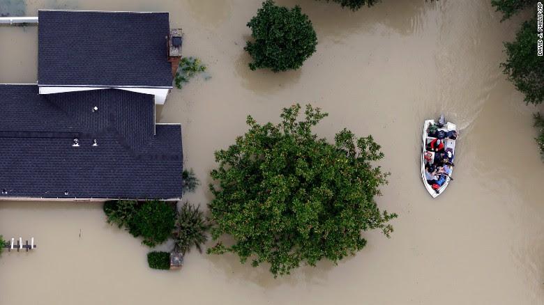 Residents evacuate their homes Tuesday near the Addicks Reservoir in Houston.
