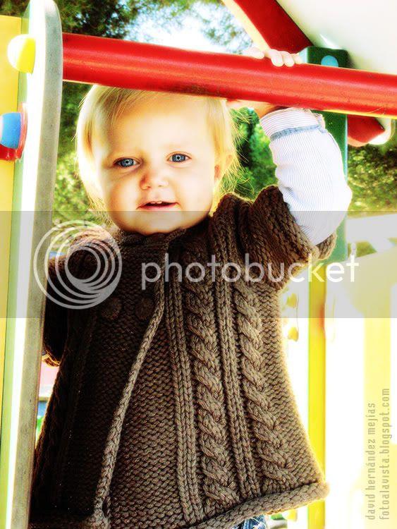 Una niña sonrie feliz subida a un tobogán