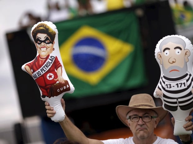 A demonstrator holds inflatable dolls depicting Brazil's former president Luiz Inacio Lula da Silva, right, and Brazil's President Dilma Rousseff during a protest calling for the impeachment of Rousseff near the National Congress in Brasilia on Sunday, Dec. 13, 2015. The words on the Dilma doll read,