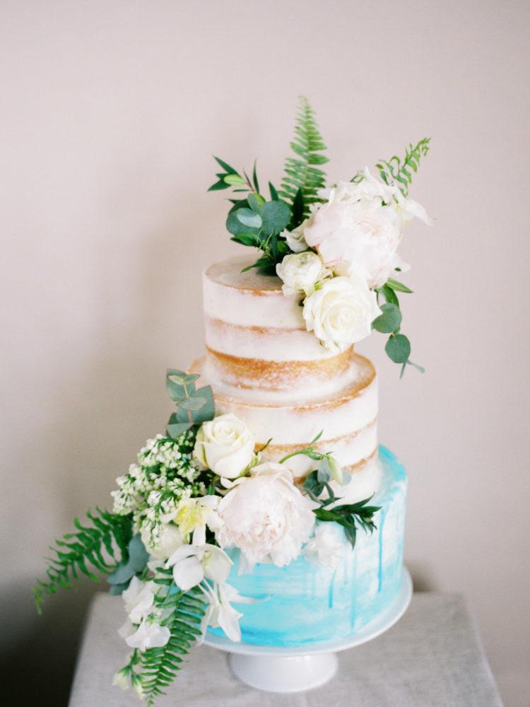 Der naked Hochzeitstorte hatte eine Blaue Schicht und Neutrale Blüten und grün zu entsprechen, die Schießen
