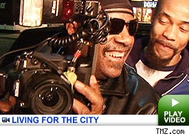 Stevie Wonder holding the paparazzi's camera with a huge smile on his face