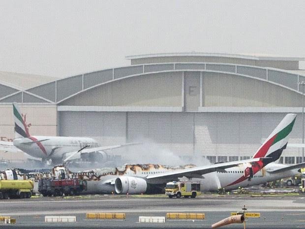 Bombeiros combatem o fogo após um avião da Emirates Airlines fazer um pouso forçado e acabar destruído durante a manhã no aeroporto de Dubai, nos Emirados Árabes Unidos. As 300 pessoas que estavam a bordo da aeronave foram retiradas em segurança (Foto: Reuters/Stringer)