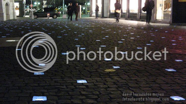 Calle de Ginebra de noche con baldosas iluminadas con saludos en diversos idiomas